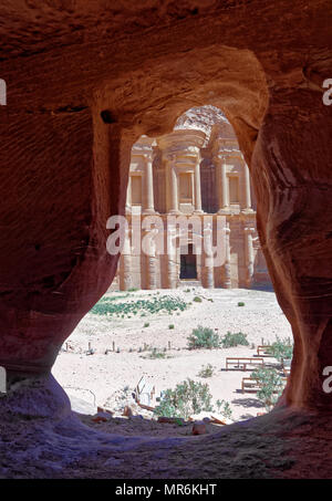 View through the rock window of a storage room in Petra to the monastery Al-deir, Jordan - Stock Photo