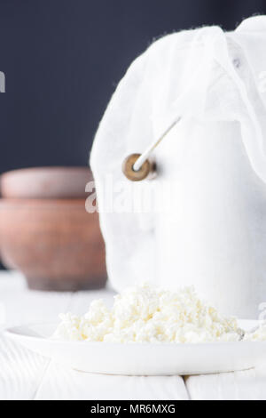 close-up view of fresh healthy cottage cheese and metal bucket behind on wooden table - Stock Photo