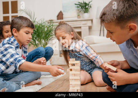 multicultural group of children playing blocks wood game together at home - Stock Photo