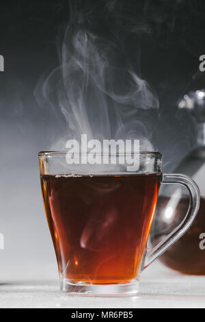 Steaming black tea in glass cup on table - Stock Photo