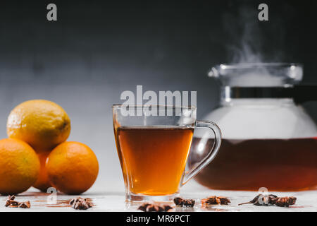 Cup of hot black tea with citrus fruits and steaming teapot - Stock Photo