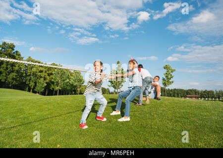 Multiethnic group of kids playing tug of war on green grass in park - Stock Photo