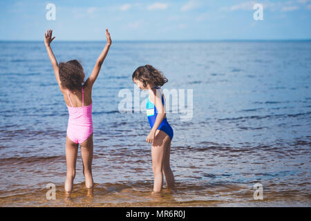 8f65e0a387 ... cute little girls in swimsuits playing at seaside together - Stock Photo