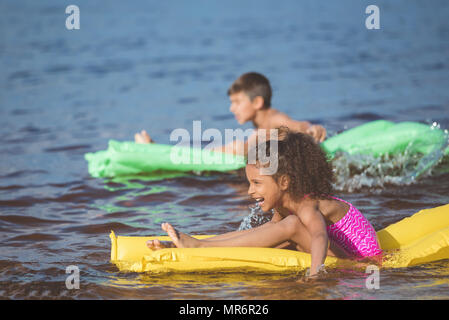side view of happy african american girl swimming on inflatable mattress at sea - Stock Photo