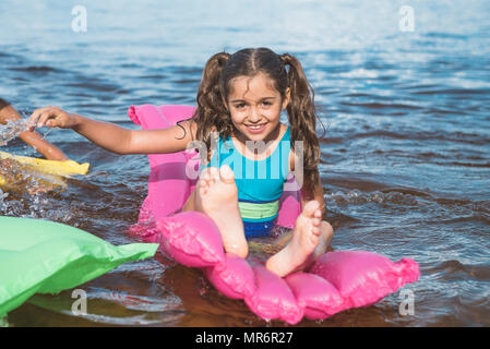 cheerful little girl swimming on inflatable mattresses at sea - Stock Photo