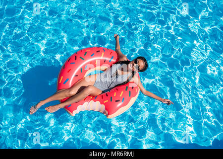Young asian woman floating on inflatable donut in swimming pool - Stock Photo