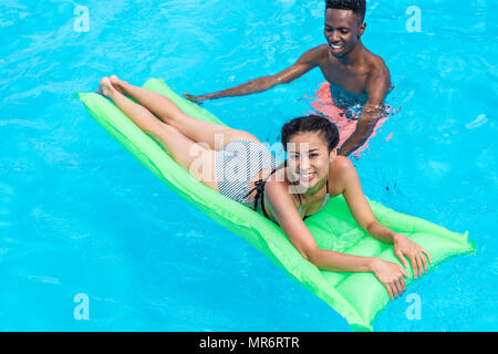 Happy young asian woman on inflatable mattress with her friend standing behind in swimming pool - Stock Photo