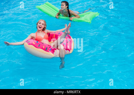 Young multiethnic women floating on inflatable mattresses in swimming pool at resort - Stock Photo