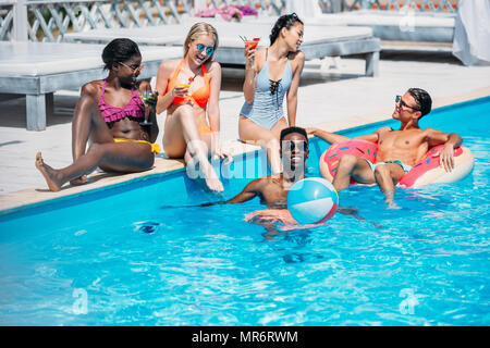 Group of young happy multiethnic people having fun together in swimming pool - Stock Photo