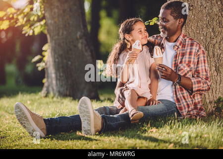 happy african american granddaughter and grandfather eating ice cream in cones while sitting on grass in park - Stock Photo