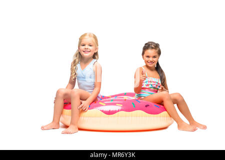9a991797f8667 ... adorable little girls in swimsuits sitting on swim tube and smiling at  camera isolated on white