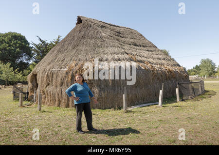 Cholchol, La Araucania, Chile: Mapuche woman stands in front of a reconstruc ted traditional communal thatch dwelling, called a ruka. - Stock Photo