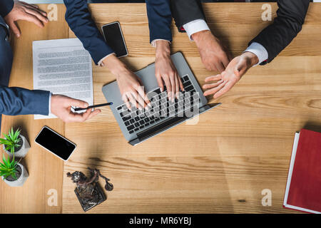 cropped shot of lawyers working on laptop together during meeting - Stock Photo