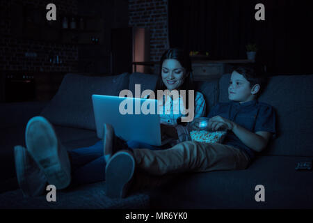 Little boy and his beautiful mother watching movie on laptop and eating popcorn, while sitting on couch - Stock Photo