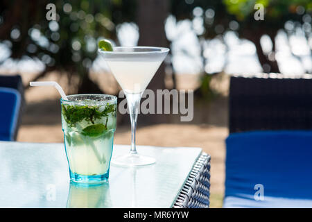 close-up shot of margarita and mojito cocktails standing on table of restaurant - Stock Photo