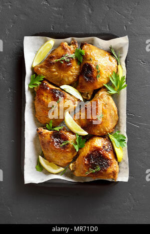 Baked chicken thighs on baking tray over black stone background. Top view, flat lay - Stock Photo