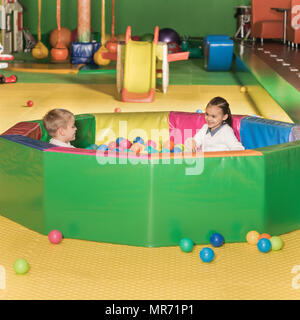 adorable happy little children playing in pool with colorful balls - Stock Photo