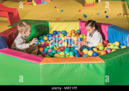 cute little kids playing in pool with colorful balls - Stock Photo