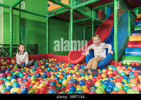 happy siblings playing in pool with colorful balls at entertainment center - Stock Photo