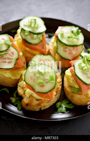 Toast sandwiches with salmon, scrambled eggs and cucumber slices - Stock Photo