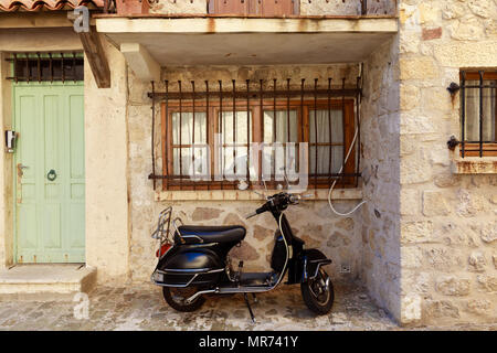 ANTIBES, FRANCE - 17 SEPTEMBER 2017: scooter parked under window of ancient building of old european town, Antibes, France - Stock Photo