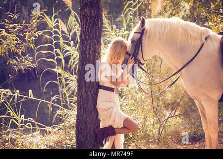 Blond girl hug her white horse in a magic light forest near river - Stock Photo