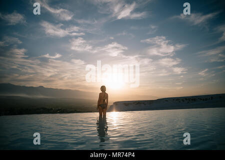back view of young woman standing in beautiful natural pool and looking at majestic landscape in pamukkale, turkey - Stock Photo