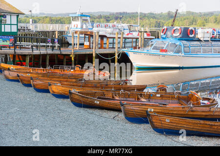 Rowing boats for hire on the side of Lake Windermere at Waterhead near Ambleside. Windermere lake Cruisers are tied up on the jetty - Stock Photo