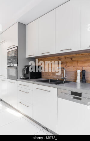 Functional kitchen with long countertop and white cabinets - Stock Photo