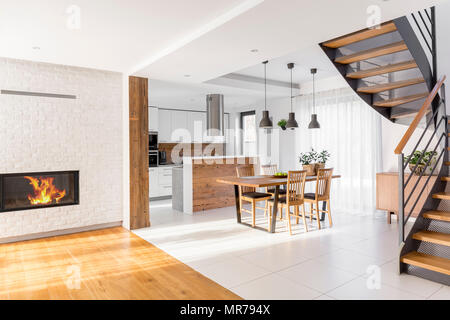 Modern luxury open plan apartment with stairs, communal table, kitchen - Stock Photo