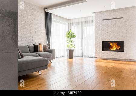 Living room with wood flooring, fireplace and sofa - Stock Photo
