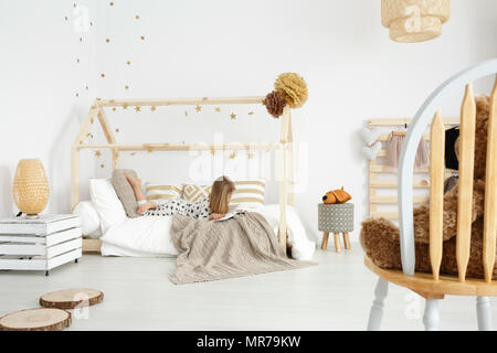 Girl reading a book on her bed in white and beige modern bedroom - Stock Photo