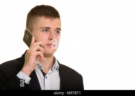 Studio shot of young businessman talking on mobile phone while t - Stock Photo