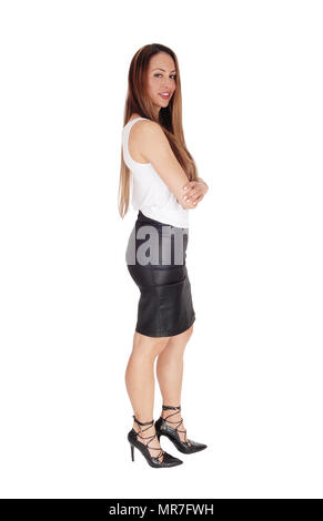 18bedb0bb3 ... Beautiful woman standing in profile in a white t-shirt and black leather  skirt and