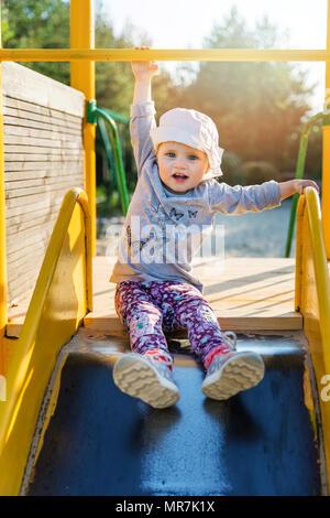 child hanging on bar at playground - Stock Photo