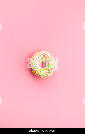 Sweet sprinkled donut on pink background. - Stock Photo