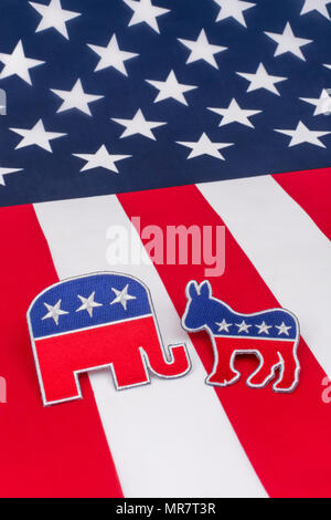 US Democrat Donkey logo & Republican elephant logo on Stars and Stripes - metaphor for 2018 US Midterm election, Midterms, and Presidential elections. - Stock Photo