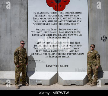 Royal Canadian Air Force Capt. Damien Miller and U.S Air Force Staff Sgt. Chelsea Rittenhouse, of the 455th Expeditionary Aeromedical Evacuation Squadron, stand in front of their artwork at Bagram Airfield, Afghanistan. The design, drafted by Miller, depicts a red poppy above the storied poem, 'In Flanders Fields.' The poem and poppy have become symbols of remembrance in Commonwealth nations. The poem was originally written by Canadian Expeditionary Force Lt. Col. John McCrae following the Second Battle of Ypres in World War I, 1915. - Stock Photo