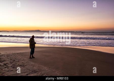 Silhouette of a man standing on Lagoinha Beach at dusk. Florianopolis, Santa Catarina, Brazil. - Stock Photo