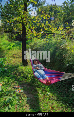 A lady relaxing in hammock - photographed at Tirthan Valley (Himachal Pradesh) - Stock Photo