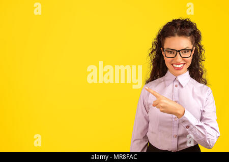 Young formal woman in eyeglasses smiling at camera and pointing away on bright yellow backdrop. - Stock Photo