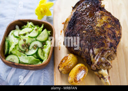 Moroccan roasted leg of lamb served with baby potatoes and green salad - Stock Photo