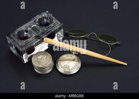 Old fountain pen and inkwell with silver coins and pocket watch on a black textured background - Stock Photo