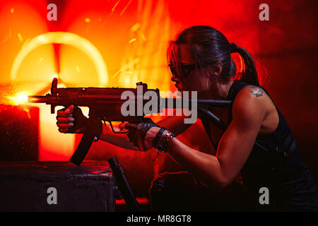Young strong woman warrior shooting from machine gun in dramatic urban night scene. Tattoo on body. - Stock Photo