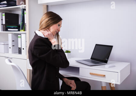 Mature Businesswoman Suffering From Neck Pain In Office - Stock Photo