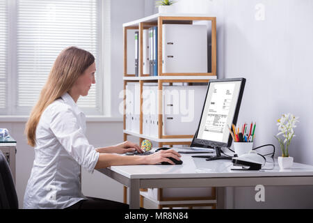 Side View Of A Businesswoman Checking Invoice On Computer At Workplace - Stock Photo