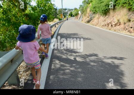 Two children walking on the road down from Castle Hill, Castle Hill QLD 4810, Australia - Stock Photo