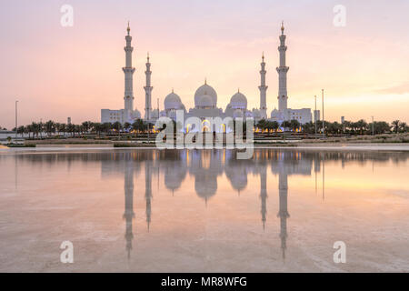 Sunset over Sheikh Zayed Grand Mosque in Abu Dhabi, United Arab Emirates - Stock Photo