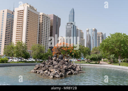 Park on Abu Dhabi Corniche Street with views of high rise buildings from a park with lake - Stock Photo