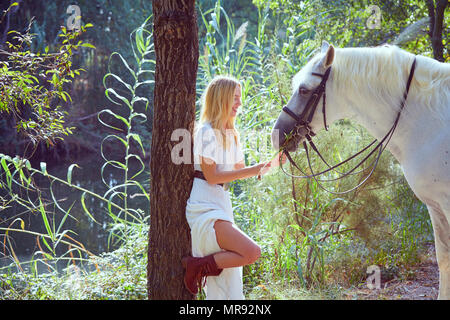 Blond girl feed grass to her white horse in a magic light forest near river - Stock Photo